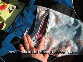 Die hintere Außentasche. Der Reißverschluß wurde zwischen Oberstoff und Futter eingesetzt. Das finde ich eleganter. In der offenen Tasche eine Schlaufe mit kleinem Karabiner für Portmonaie oder Schlüssel. Die Eingriffseite mit rotem Panesamt hinterlegt.