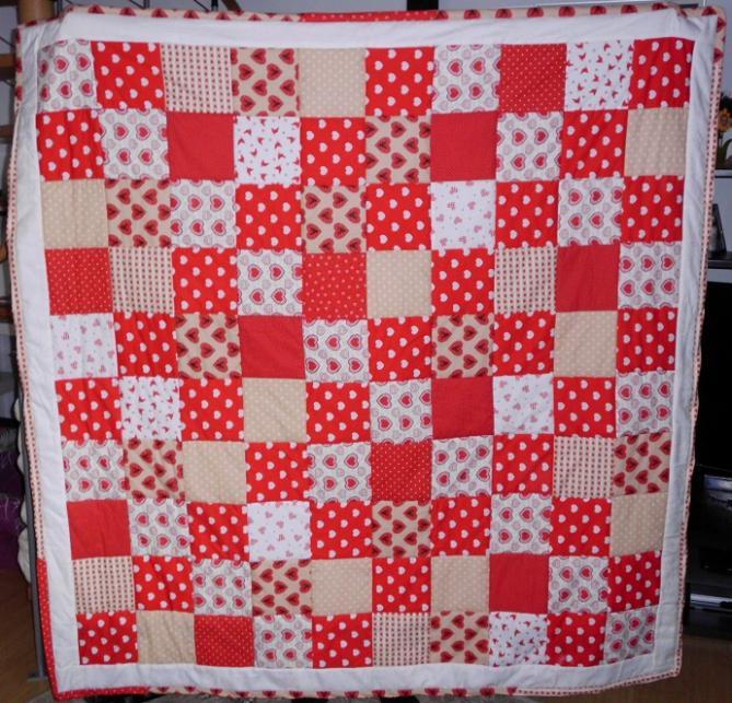 Patchworkdecke in rot-weiß-beige.