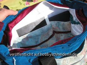 Innen auf der einen Seite die lange Tasche, dreigeteilt. im Außenstoff das Jeansthema noch einmal aufgegriffen. Dazu aus dem roten Samt noch ein elastisches Band (an den Taschentrennähten gesichert) um z.B. Flaschen ein wenig an Position zu halten oder be
